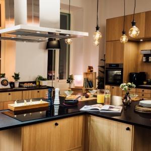 W tej propozycji połączono czarny blat, z frontami w kolorze drewna, które wieńczą okrągłe, czarne uchwyty. Nad blatem zawisło oświetlenie idealnie pasujące do męskiej kuchni - edisonowskie żarówki na odsłoniętych oplotach. Fot. IKEA.