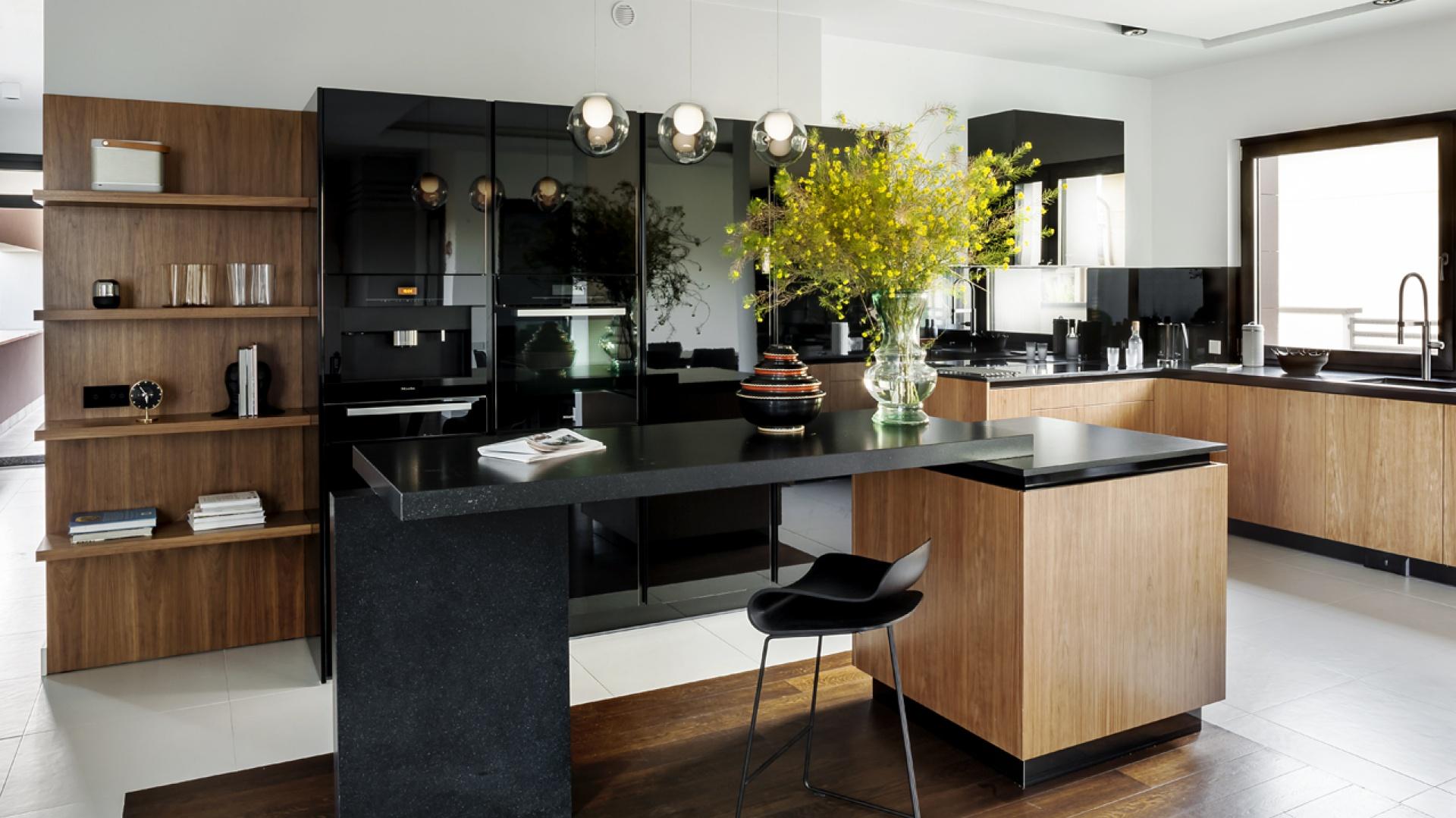 Fronty w wysokim połysku, czarny lacobel nad blatem oraz czarny blat stanowią wysmakowaną kompozycję z fornirowanymi elementami zabudowy oraz drewnianą podłogą. Fot. Zajc Kuchnie, kuchnia Z1.
