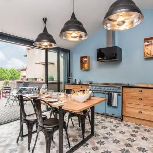 Wzorzyste płytki, niebieska farba na ścianie oraz harmonizujący z nią kolorystycznie sprzęt AGD. Do tego drewniane meble i krzesła w industrialnym stylu sprzed lat. Taka aranżacja o kwintesencja retro i vintage. Fot. Falcon.