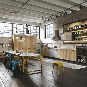 Wystrój wnętrza tej kuchni ma wszystko to, co potrzebne aby stworzyć klimat retro. Postarzane kolorowe stół i krzesła, drewniana zabudowa kuchenna i tradycyjny okap ścienny. Całość tworzy aranżację kuchni w stylu vintage z delikatnym loftowym sznytem. Fot. Snaidero.