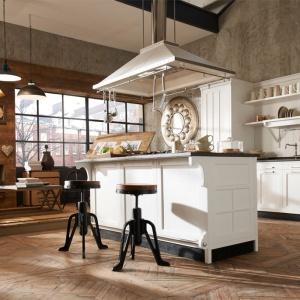 Białe, stylizowane meble kuchenne z frezowaniami na frontach stoją na niewielkich nóżkach. Towarzyszą im stylizowane na stare stołki, które podkreślają charakter wystroju kuchni. Fot. Marchi Group.
