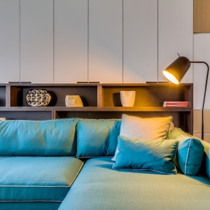 Drewno i biel ożywiono mocnym, turkusowym akcentem w postaci mebli wypoczynkowych. Projekt: Archlin Studio.