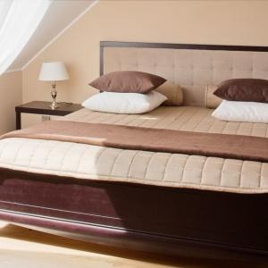 Drewniane łóżko z zagłówkiem wykończonym miękką, beżową tkaniną. Całość w zestawieniu z jasną kolorystyką ścian sprawia, że wnętrze sprzyja wypoczynkowi. Fot. Dekoria.