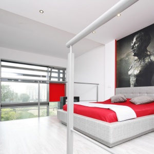 Na antresoli urządzono sypialnię, która jest przestronna i jasna. Jej otwarcie na całe mieszkanie wprowadza do wnętrza mnóstwo światła, wpadającego przez panoramiczne okna. Projekt: Monika Olejnik. Fot. Bartosz Jarosz.