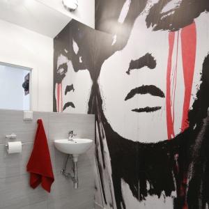 Tapeta z wizerunkiem kobiecej twarzy to odważny element wystroju wnętrza. Czerwień na grafice nawiązuje do detali, przewijających się przez całe mieszkanie. Projekt: Monika Olejnik. Fot. Bartosz Jarosz.