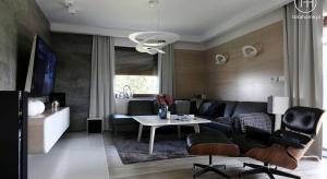 Kolorystyka bieli i szarości spójnie przewija się, przez każde pomieszczenie w tym domu, przytulności wnętrzu zapewnia drewno dębowe w jasnym wybarwieniu. Klarowność form oraz stonowana paleta barw stanowi idealne tło dla designerskich lamp. Fun