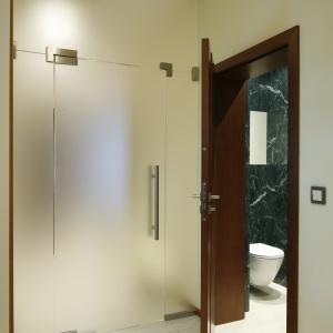 Podłoga w toalecie gościnnej i holu jest wykonana z tych samych marmurowych płytek. Podkreśla to spójny charakter strefy dziennej. Fot. Bartosz Jarosz.