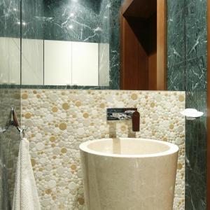 Duże, przyklejone do ściany lustro powiększa optycznie małą toaletę dla gości. Nad zabudową stelaża sedesu została wykonana szafka. Fot. Bartosz Jarosz.