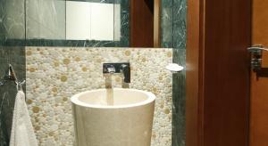 Dostojny i szlachetny. Marmur to materiał z klasą. Gdy ma jeszcze niepowtarzalny kolor, zachwyca i zaskakuje mocnym charakterem. Do wykończenia tej łazienki gościnnej użyto marmurów zielonego i beżowego.