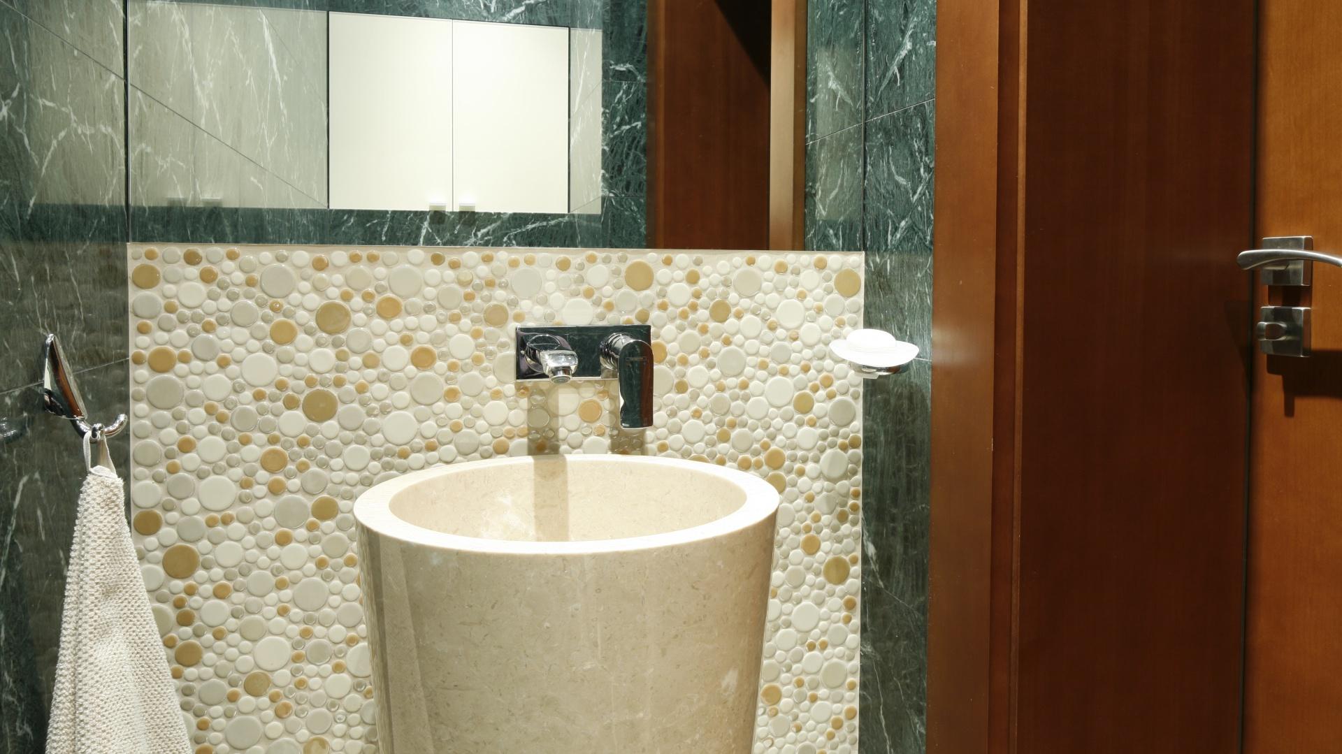 WC dla gości ma tylko 2 metry. Wykończono ją beżowymi zielonym marmurem. Fot. Bartosz Jarosz.