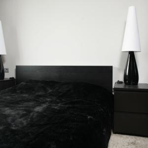 Elegancka sypialnia utrzymana w czarno-białej tonacji. Lampy z jasnym abażurem dodają lekkości ciemnym meblom. Projekt: Lucyna Kołodziejska. Fot. Bartosz Jarosz.