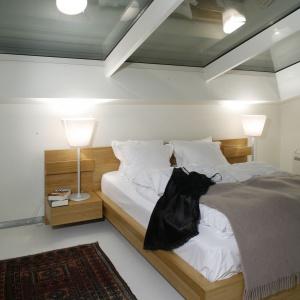 Jasna sypialnia na poddaszu. Transparentny sufit prezentuje się bardzo elegancko, jednocześnie zapewnia dużo naturalnego światła. Projekt: Ovotz Design Lab. Fot. Monika Filipiuk-Obałek.