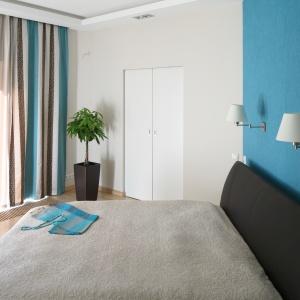 Białe wnętrze można ożywić zdecydowanymi kolorami. Ściana za łóżkiem wykończona turkusowym kolorem przyciągnie uwagę. Ponadto idealnie komponuje się z łóżkiem z tapicerowanym zagłówkiem. Projekt: Monika i Adam Bronikowscy. Fot: Bartosz Jarosz.