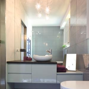 Ta łazienka jest dwa razy większa, dzięki przyklejeniu lustra bez ram na prawie całej ścianie, lśniącym płytkom i podwieszanej szafce podumywalkowej. Projekt: Arkadiusz Grzędzicki. Fot. Bartosz Jarosz.