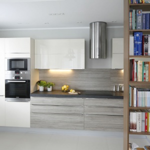 Architekci chcieli stworzyć przestronną, niezagraconą przestrzeń. Kuchnię od salonu oddziela jedynie ażurowa biblioteczka. Projekt: Joanna Morkowska-Saj. Fot. Bartosz Jarosz.