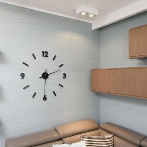 Zegar w salonie pełni funkcję dekoracyjną i praktyczną zarazem. Pozbawiony tarczy jest zamontowany bezpośrednio do ściany. Projekt: Joanna Morkowska-Saj. Fot. Bartosz Jarosz.