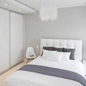 Tapicerowane tkaniną łóżko oraz pierzasta lampa ociepla nieco chłodną w wyrazie aranżację sypialni. Jednocześnie jasne barwy oraz proste w formie meble dają wrażenie lekkości i przestronności. Projekt: Małgorzata Galewska. Fot. Bartosz Jarosz.