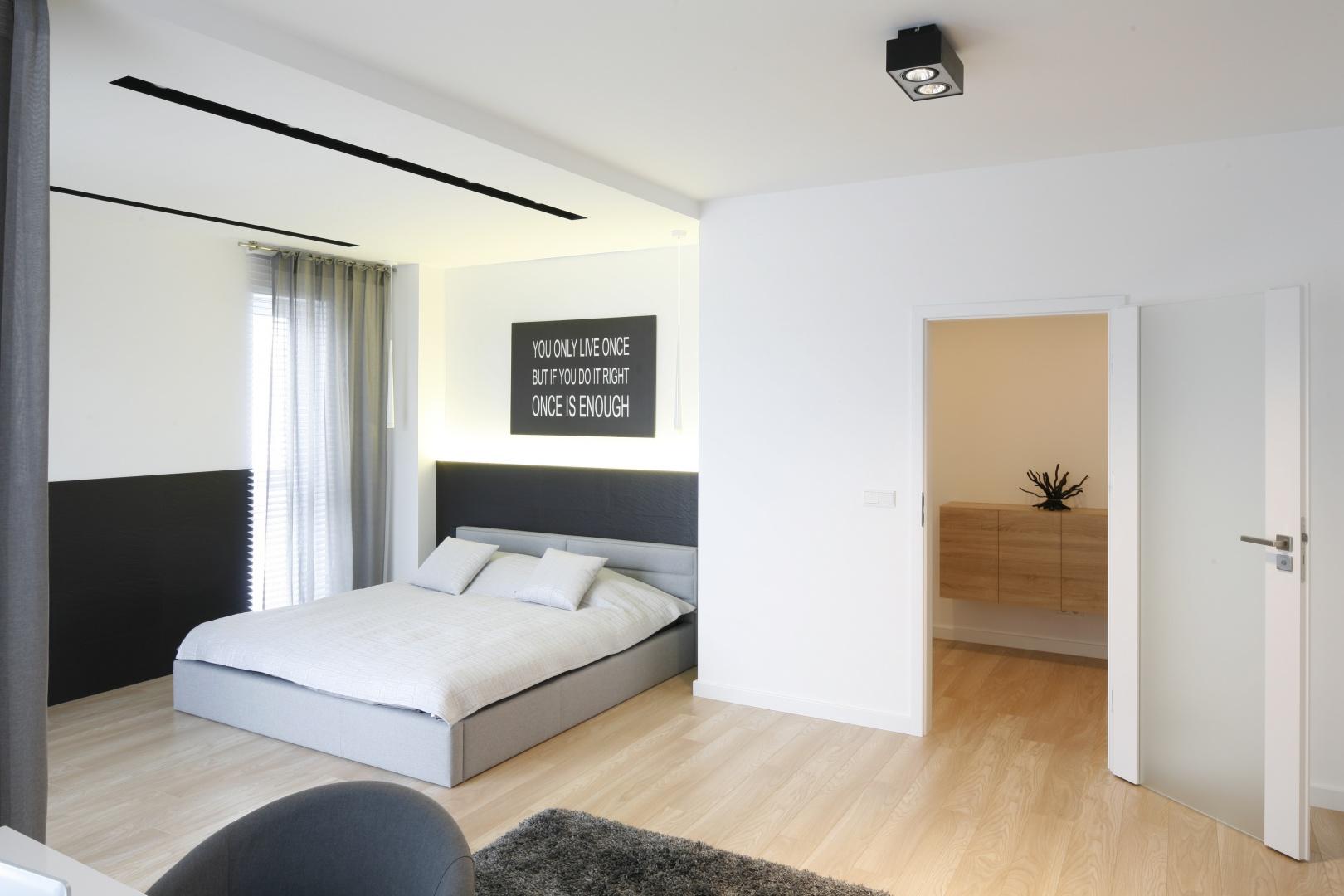 Sypialnia urządzona w minimalistycznym stylu. Meble oraz dekoracje ograniczono tu do minimum. W zasadzie jedynym elementem wnętrza jest łóżko oraz oszczędny w wyrazie obraz. Projekt: Karolina Stanek-Szadujko, Łukasz Szadujko. Fot. Bartosz Jarosz.