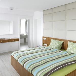 Elegancka, gustowna sypialnia z bezpośrednim dostępem do łazienki. Charakterystycznym elementem wnętrza jest ściana za łóżkiem obita tkaniną. Projekt: Dominik Respondek. Fot. Bartosz Jarosz.