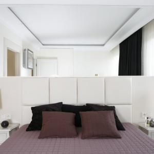 Nowoczesna sypialnia urozmaicona stylowymi dodatkami. Ściana za łóżkiem wykończona lustrem nie tylko buduje klimat wnętrza, ale też optycznie je powiększa. Projekt: Katarzyna Uszok. Fot. Bartosz Jarosz.