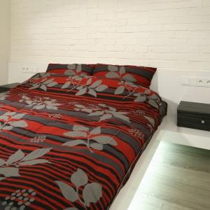 Jasna sypialnia, w której ścianę wykończono cegłą. Wnętrze jest dość małe, jednak podświetlone od dołu łóżko sprawa, że nabiera ono przestrzeni. Projekt: Dominik Respondek. Fot. Bartosz Jarosz.