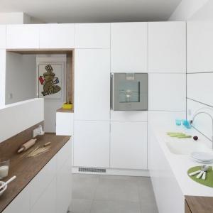 Jedną z ogromnych zalet wysokiej zabudowy kuchennej jest możliwość zastąpienia nią ściany. W tej nowoczesnej kuchni szafki okalają wnękę, prowadzącą do przedpokoju, stając się jednocześnie miejscem przechowywania i elementem działowym. Projekt: Konrad Grodziński. Fot. Bartosz Jarosz.