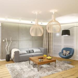 Miękki dywan w strefie wypoczynku nadaje wnętrzu przytulny charakter, a szarym kolorem harmonizuje ze ścianą za sofą. Projekt: Agnieszka Hajdas-Obajtek. Fot. Bartosz Jarosz.