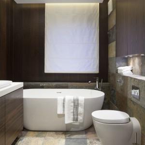 W łazience - podobnie, jak w całym domu, dominują kolory ziemi. Tutaj jednak są obecne w ciemniejszej palecie. Projekt: Agnieszka Hajdas-Obajtek. Fot. Bartosz Jarosz.