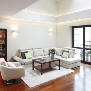 Przestronne wnętrze urządzono w bieli. Jej klasyczny charakter podkreślają meble w kolorze ciemnego drewna. Projekt: Kinga Śliwa. Fot. Bartosz Jarosz.