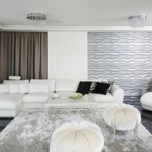 Strefę wypoczynkową organizuje duża narożna kanapa wbiałym kolorze. Fragment ściany za szezlongiem zdobią dekoracyjne panele 3D, które pomalowano na srebrny kolor. Projekt: Katarzyna Uszok. Fot. Bartosz Jarosz.