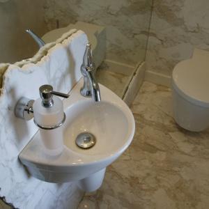 Mała toaleta wykończona tylko marmurem i lustrami. Wyjątkową dekoracją jest płyta marmurowa z nierówno ciosanymi brzegami. Proj. Daria Zaremba. Fot. Paweł Supernak