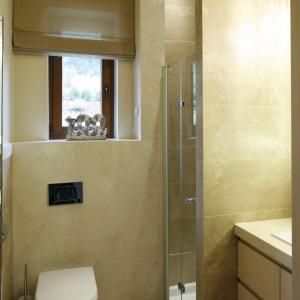 Toaleta dla gości ze ścianami wykończonymi beżowym marmurem Crema Marfil. Z tego samego kamienia jest blat podumywalkowy. Proj. Małgorzata Borzyszkowska. Fot. Bartosz Jarosz.