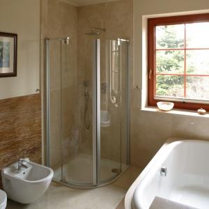 W tej niewielkiej łazience (ok. 8 m²) jasnobeżowy marmur Crema Marfil zestawiono z brązowym trawertynem Walnut. Proj. Kinga Śliwa. Fot. Bartosz Jarosz.
