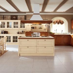Klasyczne meble kuchenne w kolorach ecru i przytulnego drewna są prostą receptą na rustykalny klimat. Tutaj dodatkowo potęguje go ciekawie udekorowany sufit, na którym pasy układają się w sposób, imitujący drewniane belki stropowe. Fot. Veneta Cucine.