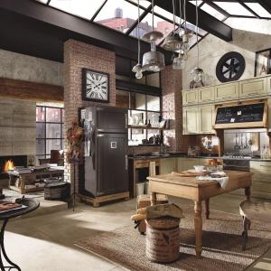 Trochę rustykalnie, trochę loftowo. Taka jest kuchnia od włoskiej marki Marchi Cucine. Cegła na ścianie, stylizowane meble i duże ilości drewna tworzą w niej rustykalny klimat. Fot. Marchi Cucine.