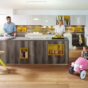 Kolor drewna w popielatym odcieniu z jaśniejszymi pasami, imitującymi przetarcia pięknie harmonizuje z żywymi elementami w postaci żółci. Fot. Schueller.