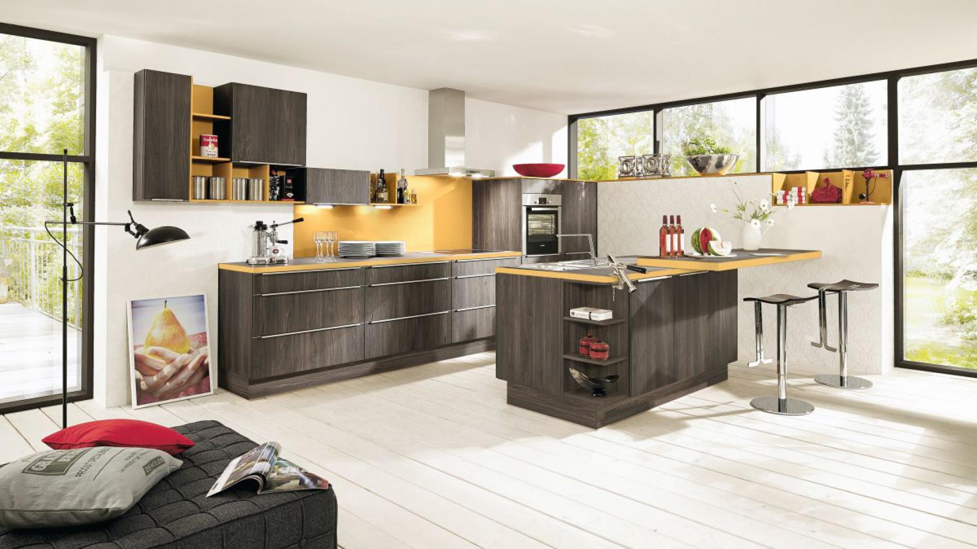 Pionowy rysunek słojów ciemnego drewna zdobi fronty tej nowoczesnej kuchni. Całość wieńczy żółty blat, kontrastujący z mocnym odcieniem drewna. Fot. Impuls, meble z programu IP 2200.
