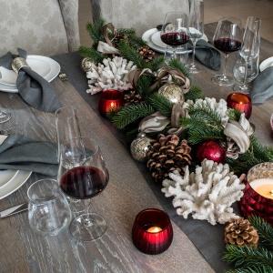 Na stole świątecznym zawsze powinno być miejsce na leśne akcenty. Szyszki i gałązki świerkowe możemy ułożyć wzdłuż centrum mebla - zastąpią wówczas tradycyjny stroik. Fot. Kelly Hoppen.