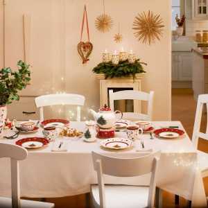 Jeśli zastawa stołowa jest bardziej zdobna, obrus może być prosty, bez koronek i haftów. Tutaj jest śnieżnobiały, a kolor wprowadza komplet pięknej porcelany ze świątecznymi motywami, utrzymanej w typowo bożonarodzeniowej kolorystyce. Fot. Rossi.pl.