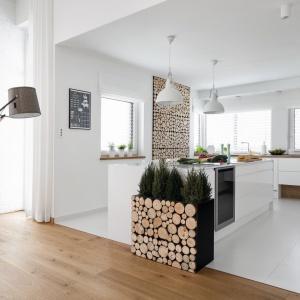 Kuchnia choć jest nowoczesna, wiele czerpie ze skandynawskiej stylistyki. Białe, nieco chłodne meble ocieplono dębowym blatem i panelem ściennym z naturalnych plastrów drewna. Projekt: Małgorzata Błaszczak. Fot. Artur Krupa.