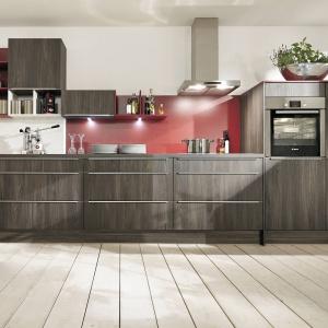 Ścianę pomalowaną na kolor czerwony zabezpieczono taflą przezroczystego szkła. Czerwień doskonale ożywia stonowaną kolorystykę kuchni. Na zdjęciu: zabudowa z linii IP 2200 marki Impuls.