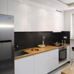Kontrast w białej kuchni wprowadza ciemna ściana nad blatem. Całość ociepla natomiast drewno zastosowane na blatach. Projekt Michał Wielecki, Artur Hoffman. Fot. Bartosz Jarosz.