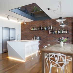 W łączonej przestrzeni kuchni i jadalni dominują geometryczne formy w postaci oryginalnej wyspy efektownie podświetlonej od dołu oraz ultra-nowoczesnych, ażurowych krzeseł. Ukoronowaniem całości jest czerwona cegła na ścianie. Projekt: B² Architecture. Fot. Michal Šeba.