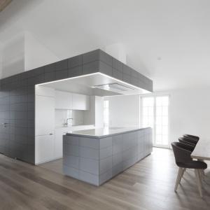 Najbardziej oryginalnym i nowoczesnym elementem otwartej strefy dziennej jest zakamuflowana kuchnia - częściowo zamknięta, częściowo otwarta, wpasowana w oryginalną zabudowę, swobodnie przechodzącą w ścianę w przedpokoju. Projekt: Destilat Design Studio. Fot. Monika Nguyen.