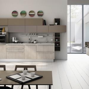Brak uchwytów na górnych szafkach sprawia, że kuchnia ma bardziej salonowy charakter. Otwarte półki urozmaicają zabudowę i ułatwiają przechowywanie często używanych przedmiotów. Na zdjęciu: meble Gayla marki Creo Kitchens. Fot. Creo Kitchen.