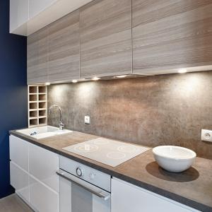 Blat laminowany imitujący beton wieńczy białe froty kuchenne na wysoki połysk. Z blatem harmonizuje dopasowana ściana nad powierzchnią roboczą oraz kolorystycznie dobrane fronty płytszych górnych szafek. Fot. Atlas Meble Kuchenne.