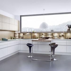 Dolną zabudowę kuchenną wieńczy subtelny delikatny blat, który wizualnie wpisuje się w jasną kolorystykę kuchni - jest on bowiem wykonany z mlecznego szkła. Fot. Leicht.