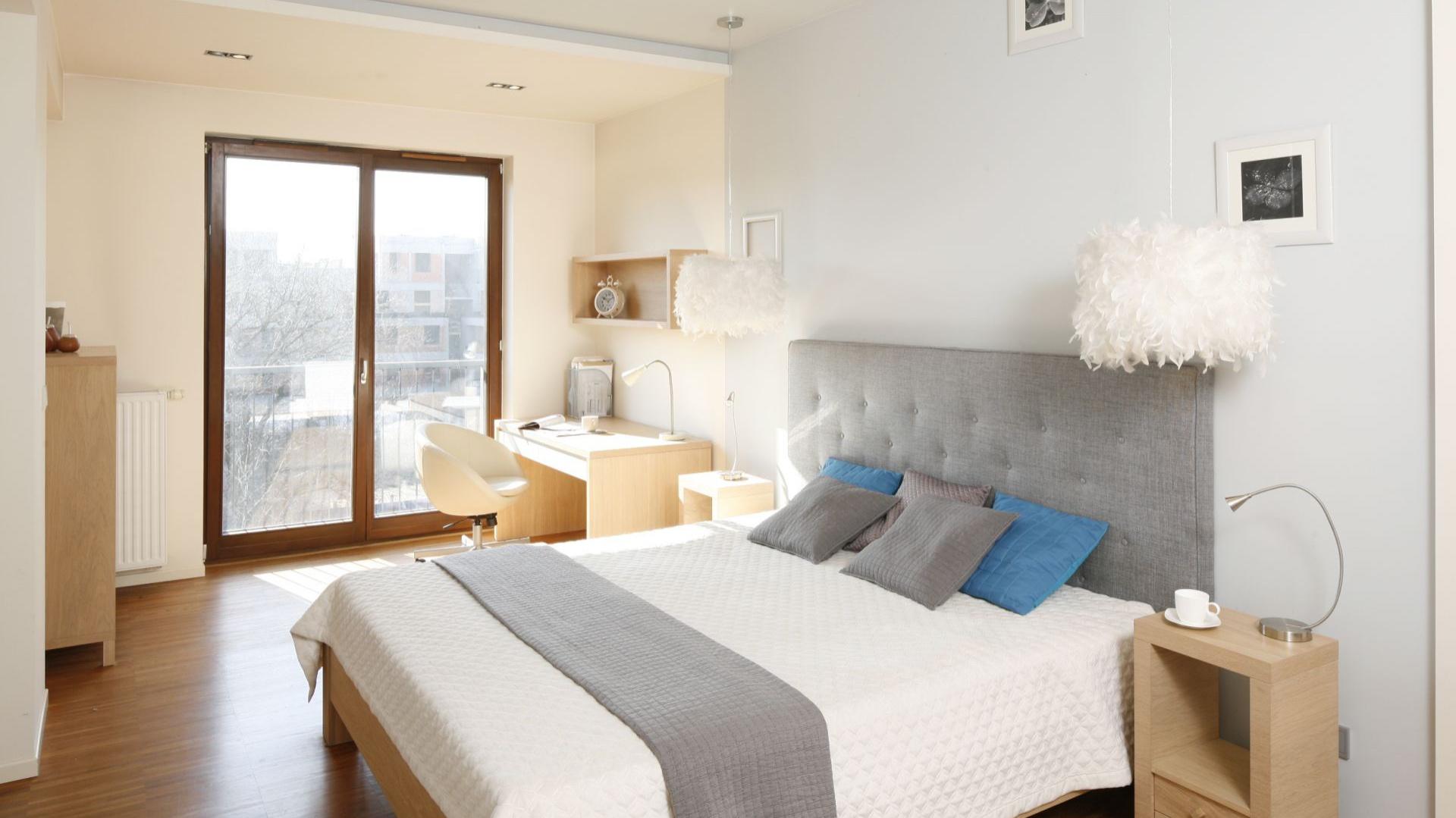 Aranżacja sypialni jest bardzo jasna i słoneczna. Nieosłonięte okna wpuszczają do wnętrza bardzo dużo światła. Jasne kolory, miękkie tkaniny i naturalne drewno nadają jej nieco skandynawski styl. Projekt: Marta Kruk. Fot. Bartosz Jarosz.