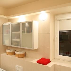 Łazienka ma małe okno, które przesłania biała roleta. Szafka nad pralką oraz sedesem i bidetem mieści przybory, środki czystości, kosmetyki. Fot. Bartosz Jarosz.