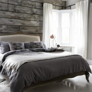 Aranżacja łóżka bez narzuty również może prezentować się okazale. Warto jednak przełamać tą powierzchnię mniejszą narzucą lub kocem, ułożonym w dole łóżka. Fot. Furniture Village.